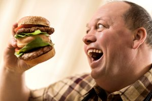 Overweight excited man about to eat a huge hamburger.