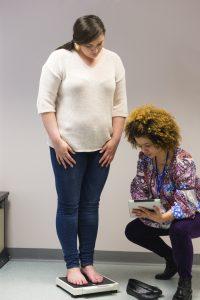 Nurse weighing woman